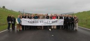 Celebrating the opening of Combe Valley Way: in the middle wearing a brown suit, ESCC leader Keith Glazier; on his right, ESCC chief executive Becky Shaw, on his left, Julian Crampton, Sea Change Sussex chairman. To the right, holding the end of the banner and wearing a blue striped tie, Rupert Clubb, director for communities, economy and transport, on his left, Carl Maynard, lead member for transport and the environment, and second from the end, Bob Pape, ESCC project manager for the road construction (photo: ESCC).