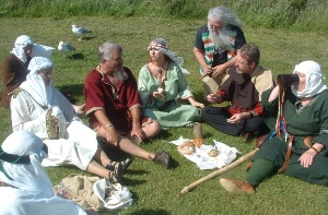 The re-enactors stop for refreshment on the pilgrims' road to the castle .