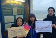 Members of Fossil Free Hastings pose outside Hastings Weather Station with a copy of the WMO report. The graph shows global temperature changes since 1880 (photo: FFH).