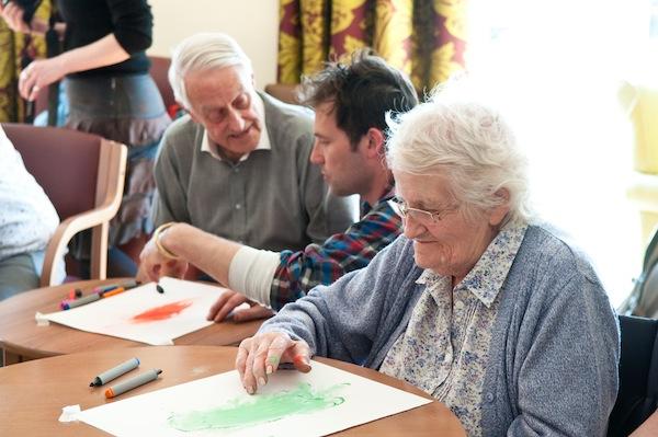 Resident John Wollatt works on his picture with art teacher Robert Sample