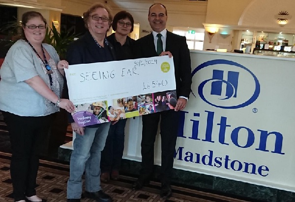 Leonardo Gagliano, general manager, and Jessica Lawrence at Hilton Maidstone present the DM Thomas Foundation for Young People grant to Tony Dart, CEO of Seeing Ear, and Luda Vanina-Dart.