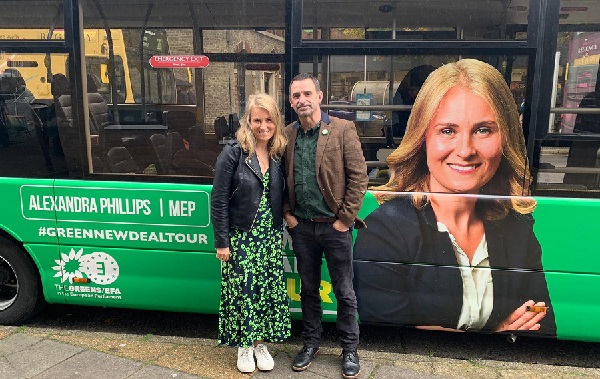 Alex Phillips poses with a colleague in front of the Green's electric bus (photo: Green Party).