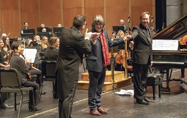 Sandwiched between conductor , left, and pianist Thomas Pandolfi, Polo Piatti takes a bow following the world premiere of his new piano work.