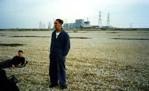Derek Jarman in his distinctive blue overalls, Dungeness, 1989 © Derek Brown.