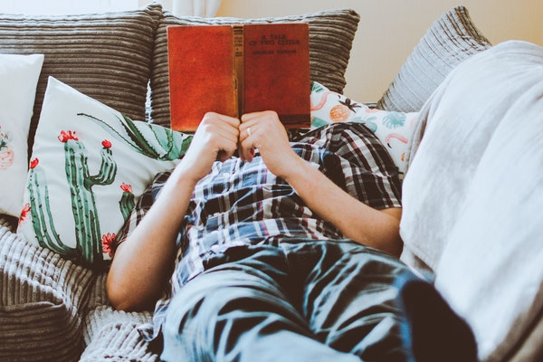 photo-of-man-lying-on-bed-while-reading-book-1485115