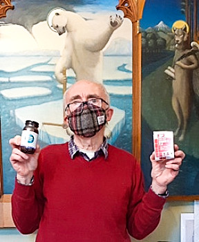 Professor Tuddenham masked and holding vitamin D supplements.